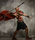 Wounded gladiator in red coat throwing spear — Stock Photo