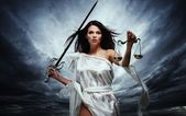 Femida, Goddess of Justice, with scales and sword against dramatic stormy sky — Stock Photo