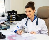 Cheerful young doctor woman in her office behind table  — Stock Photo