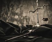 Scales and wooden hammer on judge's mantle — Stock Photo