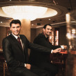 Two young men in suits behind gambling table in casino — Stock Photo #41100679