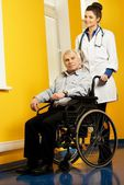 Cheerful young nurse woman with senior man in wheelchair  — Photo