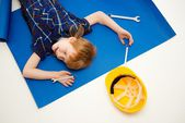 Funny little mechanic boy with wrench tools lying on a blueprint — Stock Photo