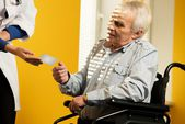 Nurse woman giving client's card to senior man in wheelchair  — Stock Photo