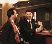 Two young men in suits behind gambling table in a casino — Stock Photo