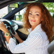 Beautiful smiling middle-aged redhead woman behind steering wheel — Stock Photo #41476283