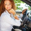 Beautiful smiling middle-aged redhead woman behind steering wheel — Stock Photo