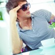 Handsome young man in sunglasses sitting on summer terrace — Stock Photo #41476405