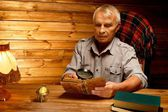 Senior man with magnifier reading vintage book in homely wooden interior  — Stock Photo