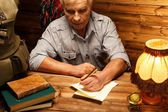 Senior writing letter with quill pen in homely wooden interior  — Stock Photo