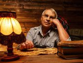 Senior man with magnifier looking at vintage map in homely wooden interior  — Stock Photo