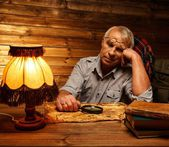 Senior man with magnifier fell asleep in homely wooden interior  — Stock Photo