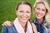 Two beautiful smiling young women in jeans jackets sitting on a bench in a park — Stockfoto
