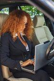 Imprenditrice bella rossa di mezza età in giacca nera con il portatile dietro il volante — Foto Stock