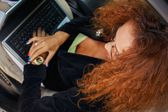 Beautiful middle-aged redhead businesswoman in black jacket with laptop behind steering wheel — Stock Photo