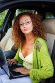 Donna bella rossa di mezza età con il portatile dietro il volante — Foto Stock