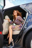 Beautiful middle-aged redhead woman in a luxury car interior  — Stock Photo