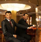 Two young men in suits behind gambling table in a casino — ストック写真