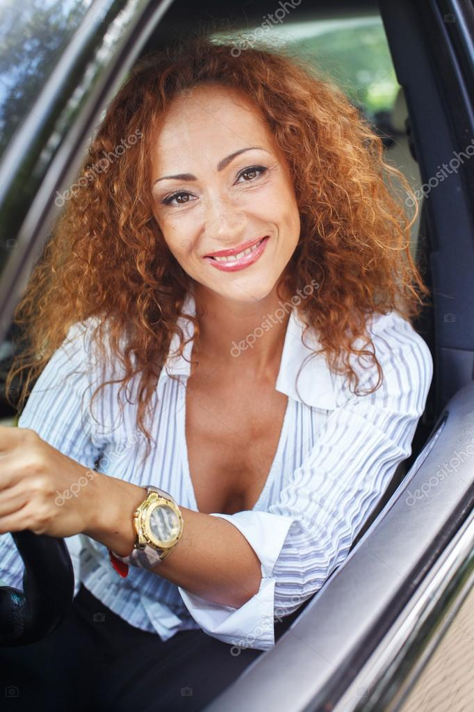 Beautiful smiling middle-aged redhead woman behind steering wheel ...