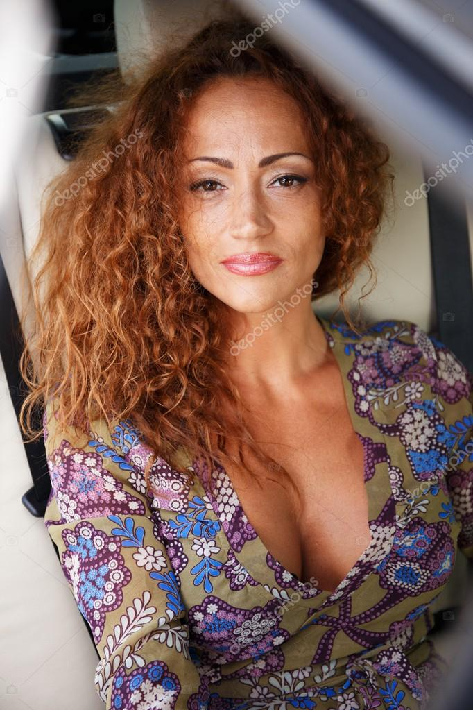 Beautiful middle-aged redhead woman in a luxury car interior ...
