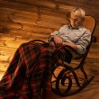 Senior man fell asleep on rocking chair in homely wooden interior — Stock Photo #41872639