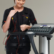 Young womin training costume near Electro Muscular Stimulation EMS machine  — Stock Photo #41872725