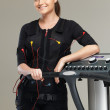 Young womin training costume near Electro Muscular Stimulation EMS machine  — Stock Photo #41872729