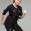 Young womdoing exercise  in Electro Muscular Stimulation EMS training costume  — Stock Photo #41872775