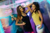 Group of happy young people dancing at night club  — Stock Photo