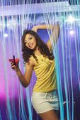 Beautiful young brunette woman in short skirt dancing at the night club  — Stock Photo