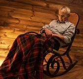 Senior man fell asleep on rocking chair in homely wooden interior  — Stock Photo