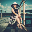 Stock Photo: Beautiful woman wearing hat and white scarf sitting on old wooden pier