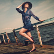 Stock Photo: Stylish woman in white hat standing on old wooden pier