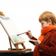 Little redhead boy drawing picture on an easel — Stock Photo