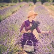 Woman in purple dress and hat with basket in lavender field  — Stock Photo #42240869