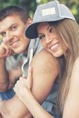 Young happy smiling sporty couple sitting on bench in a park — Stock Photo