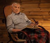 Senior man with smoking pipe sitting on rocking chair in homely wooden interior — Stock Photo