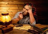 Senior man with smoking pipe in homely wooden interior  — Stock Photo