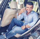 Handsome stylish man on a back seat with a mobile phone — Stock Photo