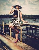 Woman in white hat and scarf standing near old pier rails  — Stock Photo