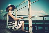 Bela mulher usando chapéu e lenço branco sentado no velho cais de madeira — Fotografia Stock
