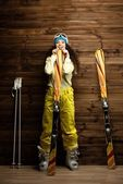 Happy woman with skis and ski boots near wooden wall  — Foto de Stock