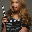 Young woman with long hair and blue eyes holding cinema clapper board — Stock Photo