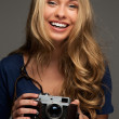 Positive young woman with long hair and blue eyes holding vintage style camera — Stock Photo #42713403