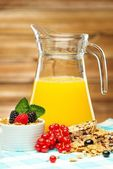 Healthy breakfast with fresh orange juice on tablecloth in wooden rural interior  — Stock Photo