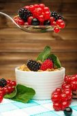 Healthy breakfast with muesli and berries on tablecloth in wooden rural interior  — Stock Photo