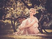 Dreaming blond retro woman in summer dress sitting on a meadow — Stock Photo