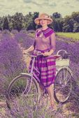 Woman in purple dress and hat with retro bicycle in lavender field — Zdjęcie stockowe