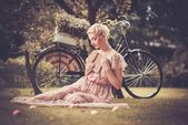 Dreaming blond retro woman with a book in summer dress sitting on a meadow — Foto Stock