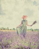 Woman in long green dress and hat in a lavender field  — Stock Photo